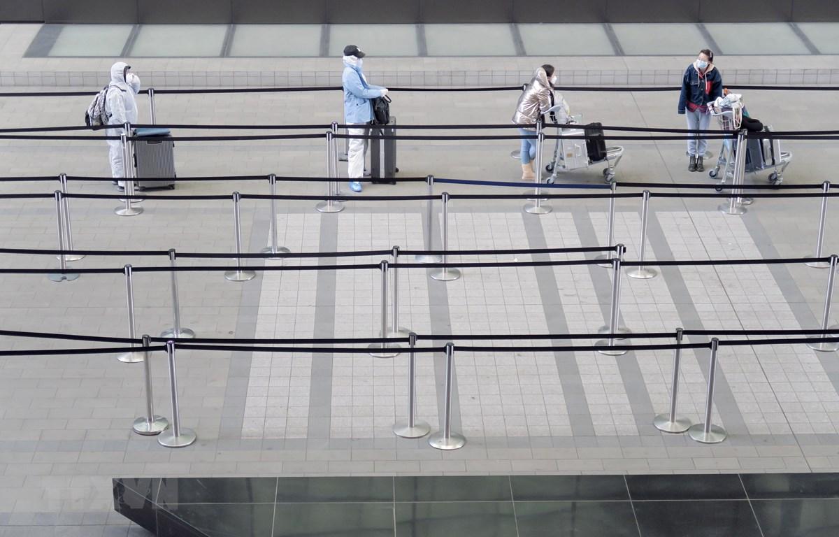 Hành khách thực hiện giãn cách xã hội phòng lây nhiễm COVID-19 tại sân bay Heathrow ở London, Anh, ngày 1/5/2020. (Ảnh: THX/TTXVN)