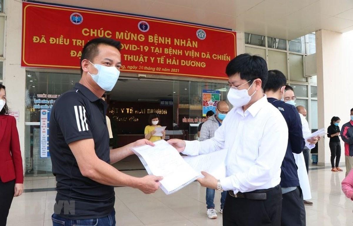 Ông Trần Trọng Khoa, Phó Cục trưởng Cục khám chữa bệnh, Bộ Y tế trao giấy ra viện cho bệnh nhân ra viện lần này. (Ảnh: Mạnh Minh/TTXVN)