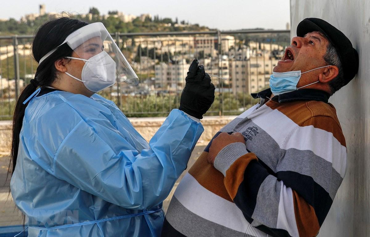 Nhân viên y tế Israel lấy mẫu xét nghiệm COVID-19 cho người dân tại Jerusalem ngày 14/12/2020. (Ảnh: AFP/TTXVN)