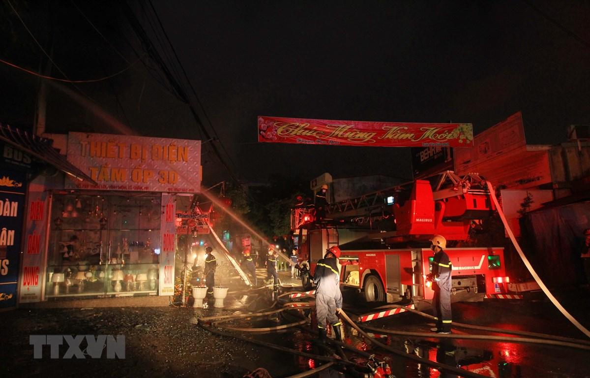 Lực lượng phòng cháy chữa cháy đang tích cực phun nước dập lửa, khống chế đám cháy. (Ảnh: An Đăng/TTXVN)