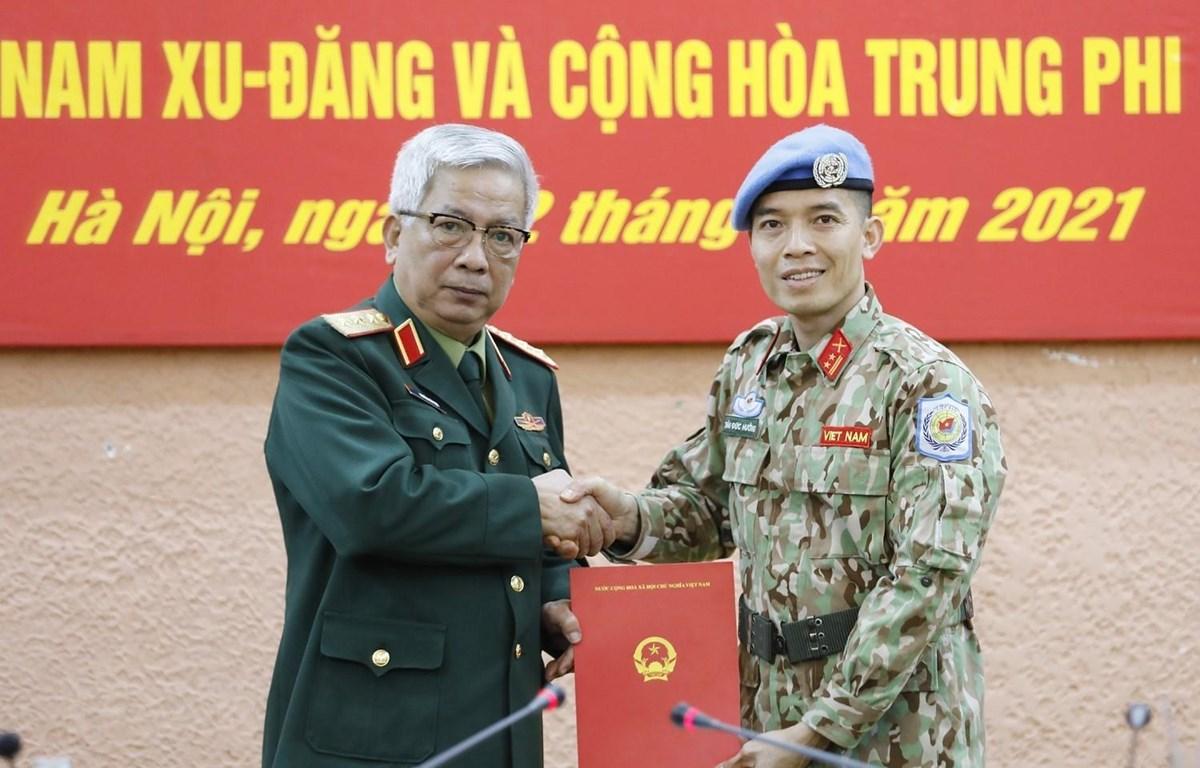 Thượng tướng Nguyễn Chí Vịnh, Thứ trưởng Bộ Quốc phòng trao Quyết định của Chủ tịch nước cho Trung tá Trần Đức Hưởng đi thực hiện nhiệm vụ tại Trụ sở Liên hợp quốc (tại New York, Hoa Kỳ). (Ảnh: Dương Giang/TTXVN)