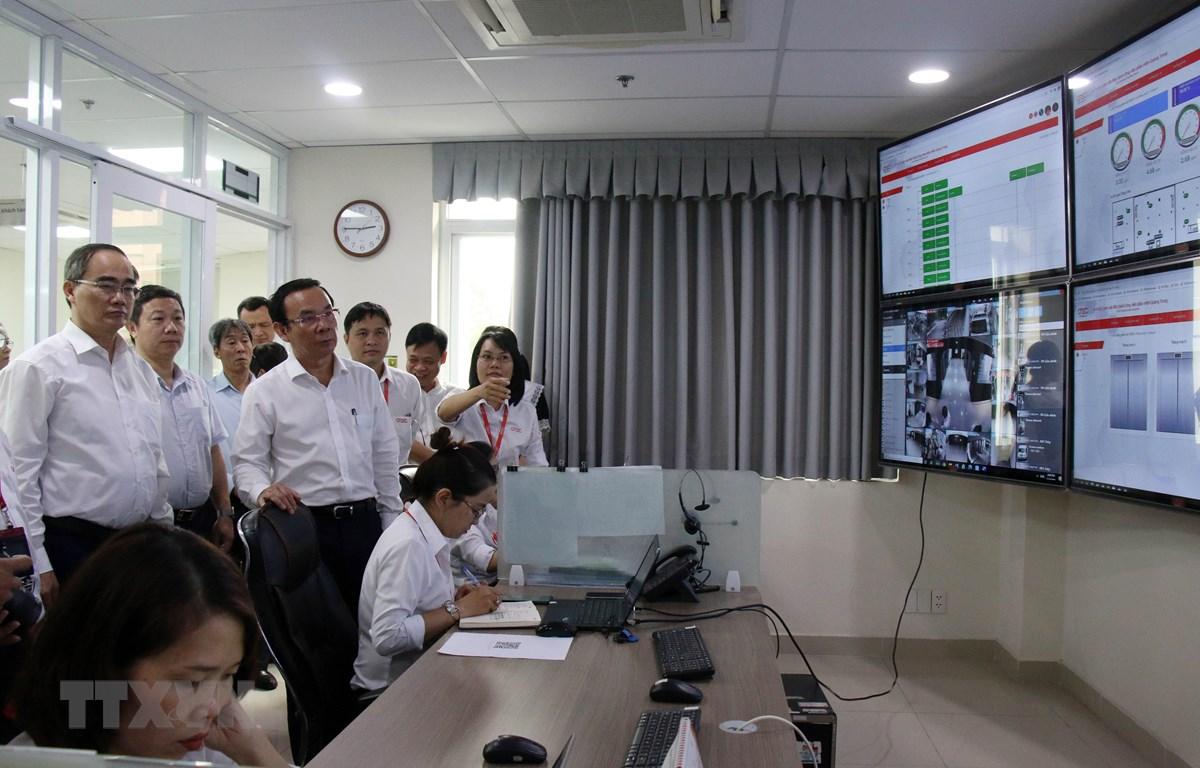 Bí thư Thành ủy Thành phố Hồ Chí Minh Nguyễn Văn Nên cùng đoàn lãnh đạo thành phố nghe giới thiệu về Trung tâm giám sát điều hành Công viên phần mềm Quang Trung. (Ảnh: Tiến Lực/TTXVN)