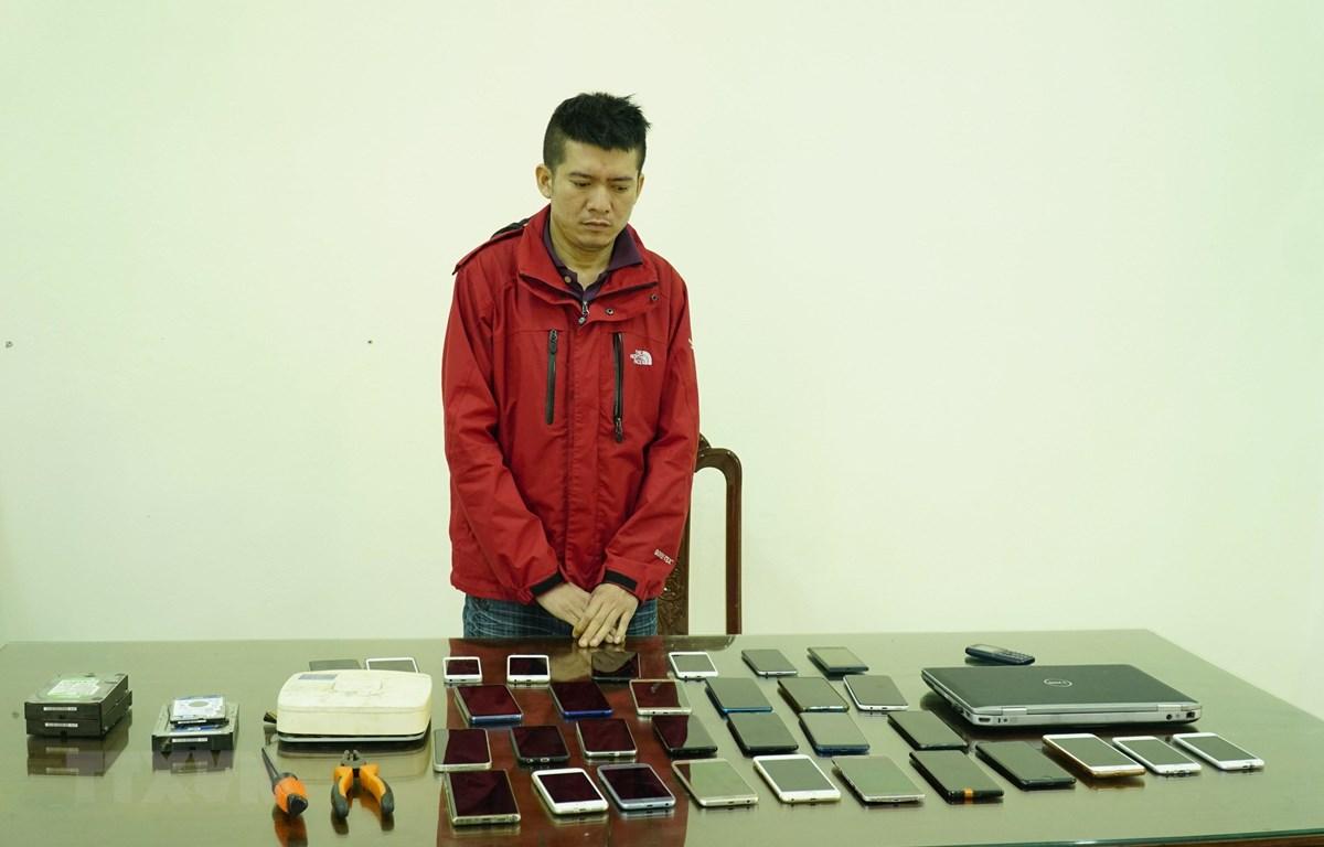 Đối tượng Nguyễn Văn Nam và tang vật tại cơ quan điều tra. (Ảnh: Xuân Tư/TTXVN)