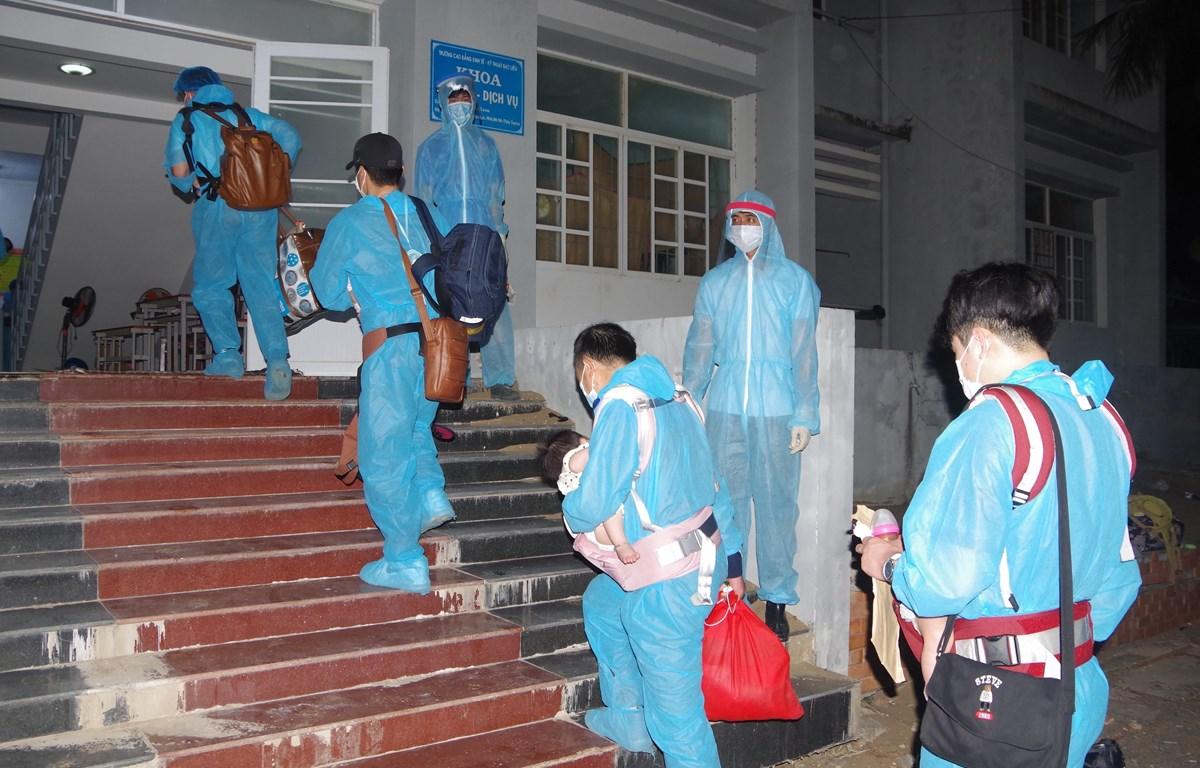 Công dân Việt Nam từ nước ngoài trở về được các nhân viên y tế hướng dẫn vào khu cách ly. (Ảnh: Chanh Đa/TTXVN)