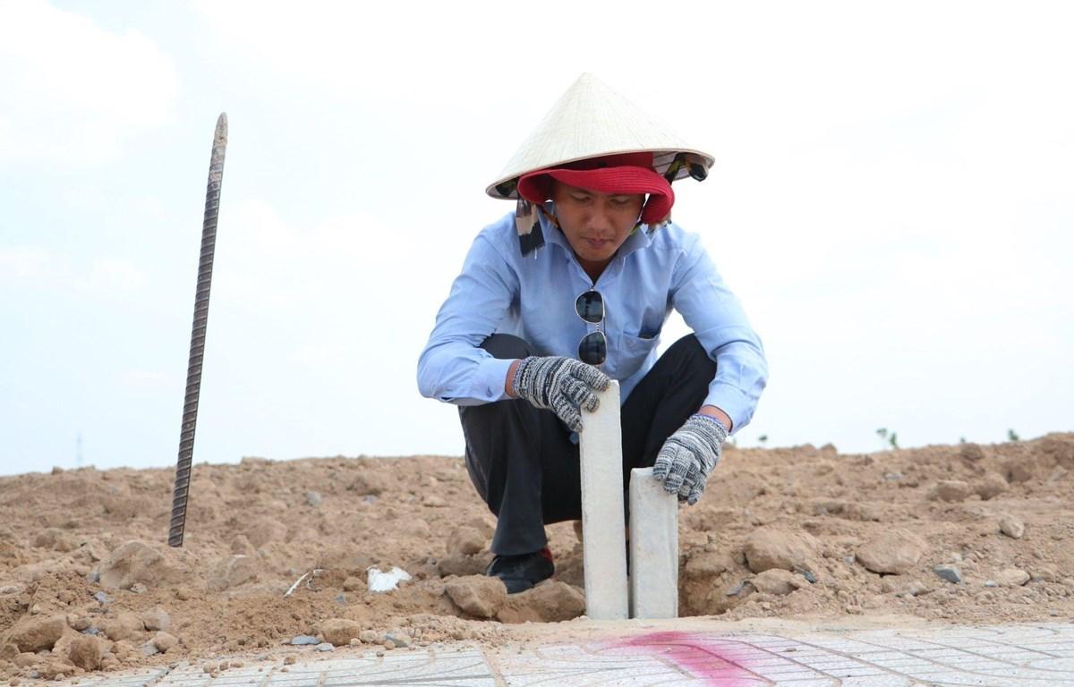 Cắm mốc nhằm xác định vị trí, diện tích các lô đất tại Khu tái định cư Lộc An-Bình Sơn. (Ảnh: Công Phong/TTXVN)