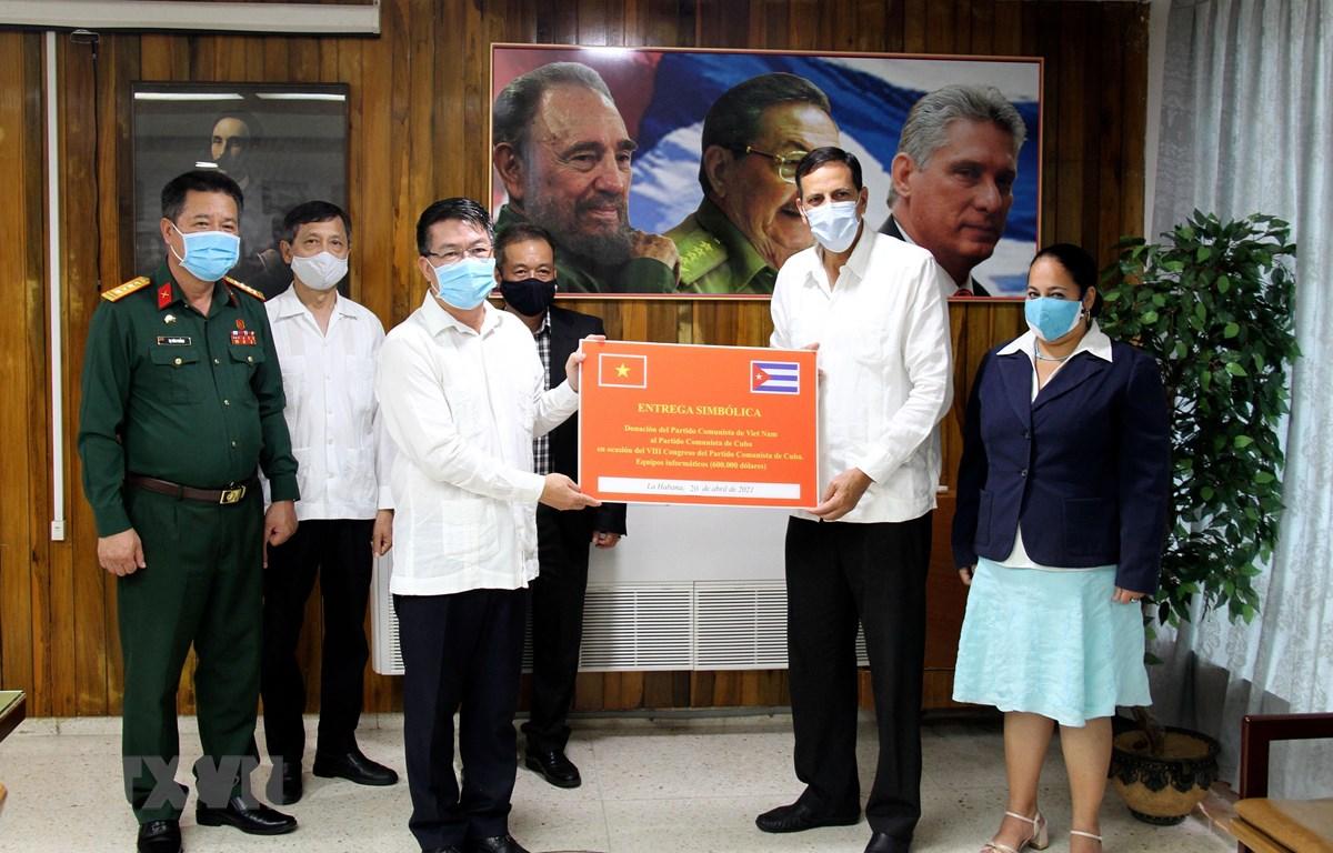Đại sứ Lê Thanh Tùng trao tượng trưng quà của Đảng Cộng sản Việtk Nam tặng Đảng Cộng sản Cuba cho Phó Trưởng ban Quan hệ Quốc tế Đảng Cộng sản Cuba Juan Carlos Marsán Aguilera. (Ảnh: Vũ Lê Hà/TTXVN)