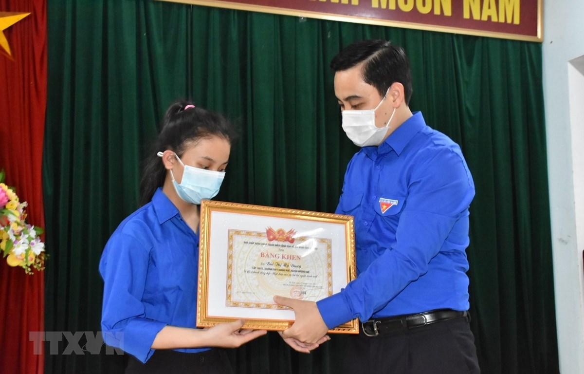 Bí thư Tỉnh đoàn Hà Tĩnh Lê Thành Đông trao tặng Bằng khen cho em Bùi Thị Mỹ Dung. (Ảnh: Hoàng Ngà/TTXVN)