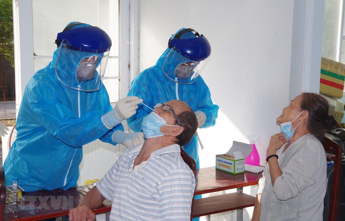 Cán bộ Trung tâm kiểm soát bệnh tật tỉnh Bạc Liêu lấy mẫu bệnh phẩm xét nghiệm sàng lọc bệnh COVID-19. (Ảnh: Chanh Đa/TXVN)