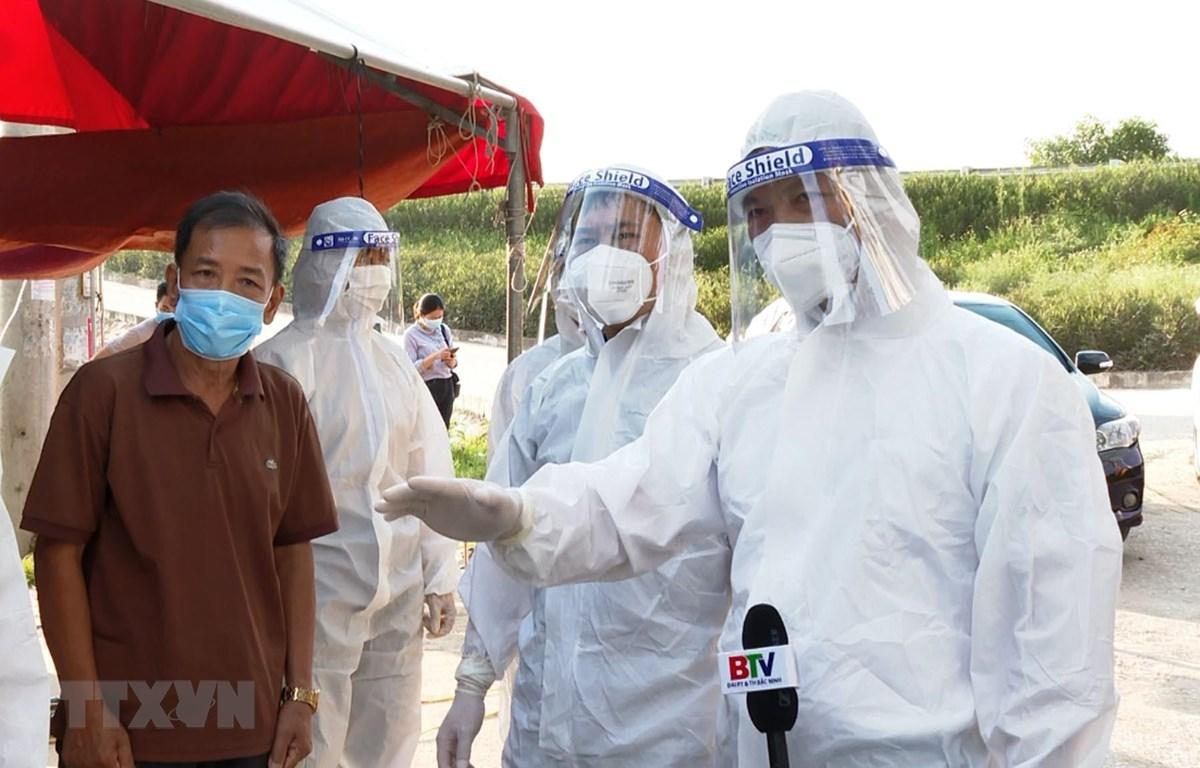 Phó Chủ tịch Thường trực UBND tỉnh Bắc Ninh Vương Quốc Tuấn (ngoài cùng bên phải) kiểm tra tại chốt kiểm dịch thôn Thụy Mão, xã Mão Điền, huyện Thuận Thành. (Ảnh: Đinh Văn Nhiều/TTXVN)