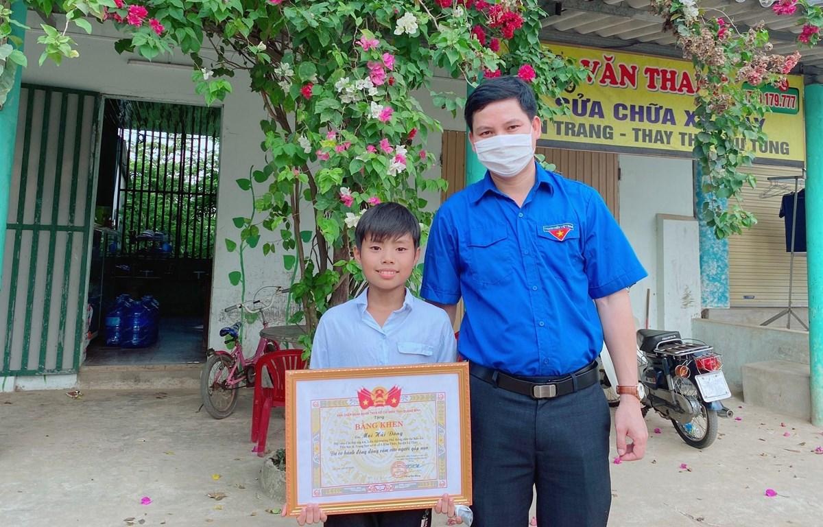 Bí thư Tỉnh đoàn Quảng Bình trao tặng Bằng khen tuyên dương hành động dũng cảm của Mai Hải Đăng. (Ảnh: Võ Dung/TTXVN)