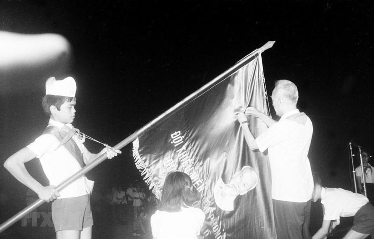 Quyền Chủ tịch Nguyễn Hữu Thọ gắn Huân chương Hồ Chí Minh lên lá cờ truyền thống của Đội Thiếu niên Tiền phong Hồ Chí Minh (1981). (Ảnh: Ngọc Quán/TTXVN)