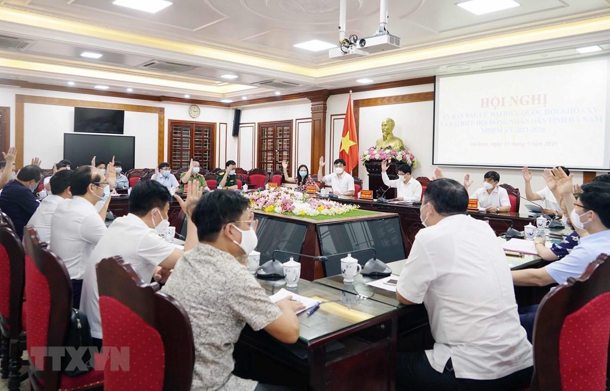 Biểu quyết thông qua Nghị quyết công bố danh sách những người trúng cử đại biểu HĐND tỉnh. (Ảnh: Nguyễn Chinh/TTXVN)
