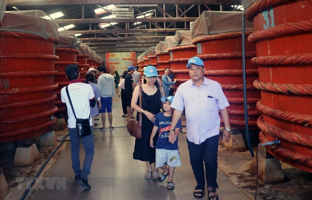 Khách du lịch tham quan khu sản xuất nước mắm tại Nhà thùng nước mắm Khải Hoàn trên đảo Phú Quốc. (Ảnh: Lê Huy Hải/TTXVN)