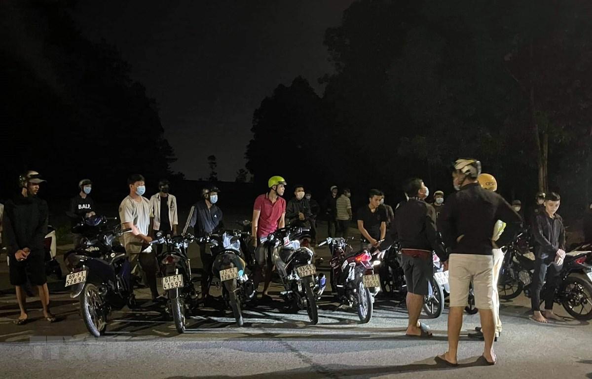 Hơn 20 thanh niên bị bắt giữ do đua xe tại Bình Dương đêm 5/6, nhiều người không đeo khẩu trang. (Ảnh: TTXVN phát)