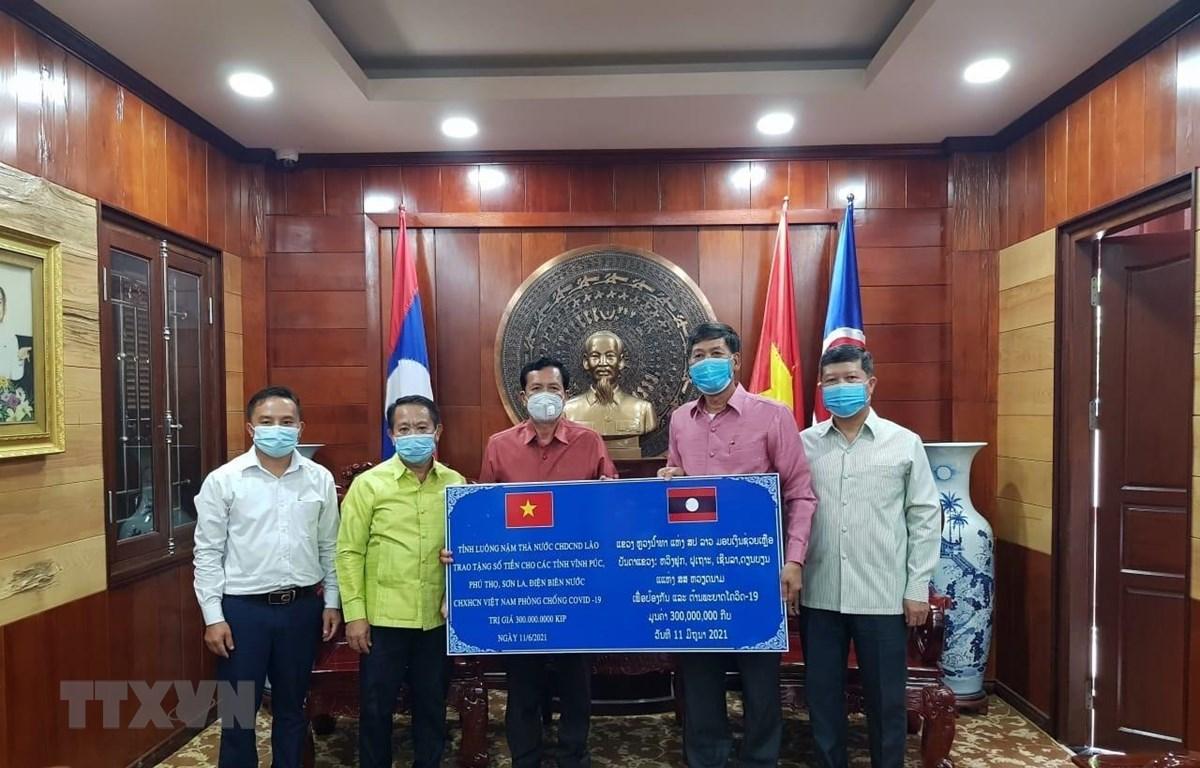 Đại diện chính quyền tỉnh Luang Namtha, Lào trao tặng tiền hỗ trợ 4 tỉnh của Việt Nam phòng chống dịch bệnh covid-19. (Ảnh: TTXVN phát)