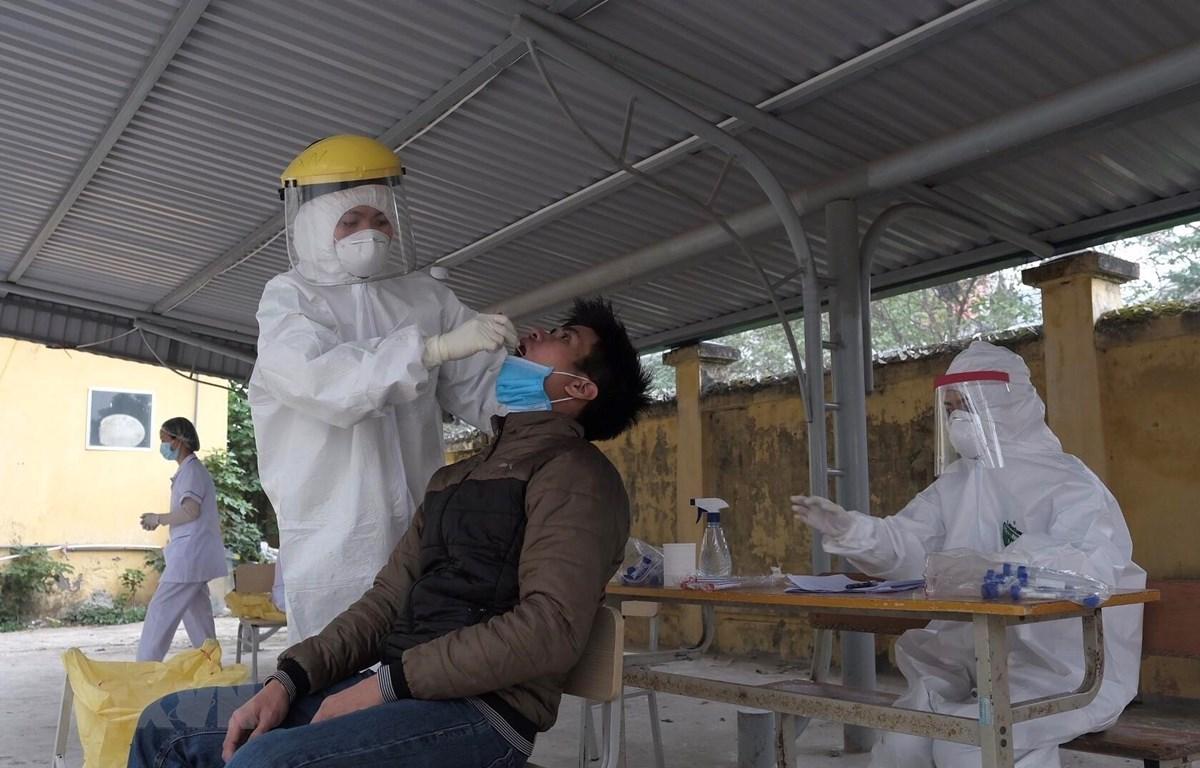 Nhân viên y tế lấy mẫu xét nghiệm COVID-19 với người có tiếp xúc gần với ca F0 tại Hà Nội. (Ảnh: Phạm Hùng - TTXVN phát)