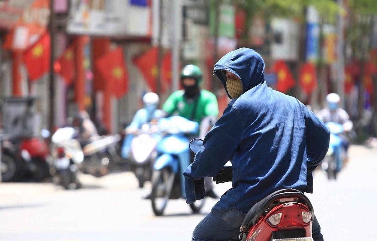 Dưới cái nóng thiêu đốt, người dân tham gia giao thông phải trang bị áo mũ chống nắng kín mít để tránh nắng. (Ảnh: Hoàng Hiếu/TTXVN)