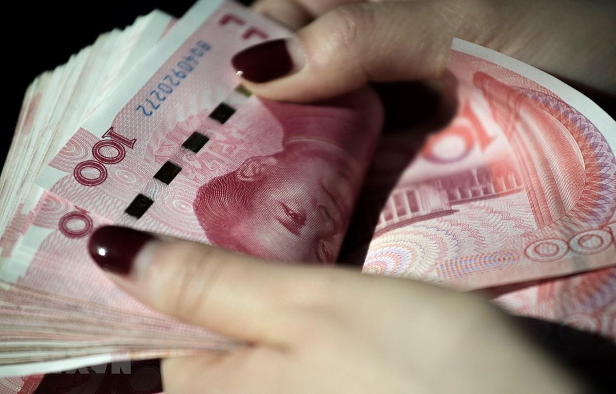 Đồng tiền giấy mệnh giá 100 Nhân dân tệ ở Bắc Kinh, Trung Quốc. (Ảnh: AFP/TTXVN)
