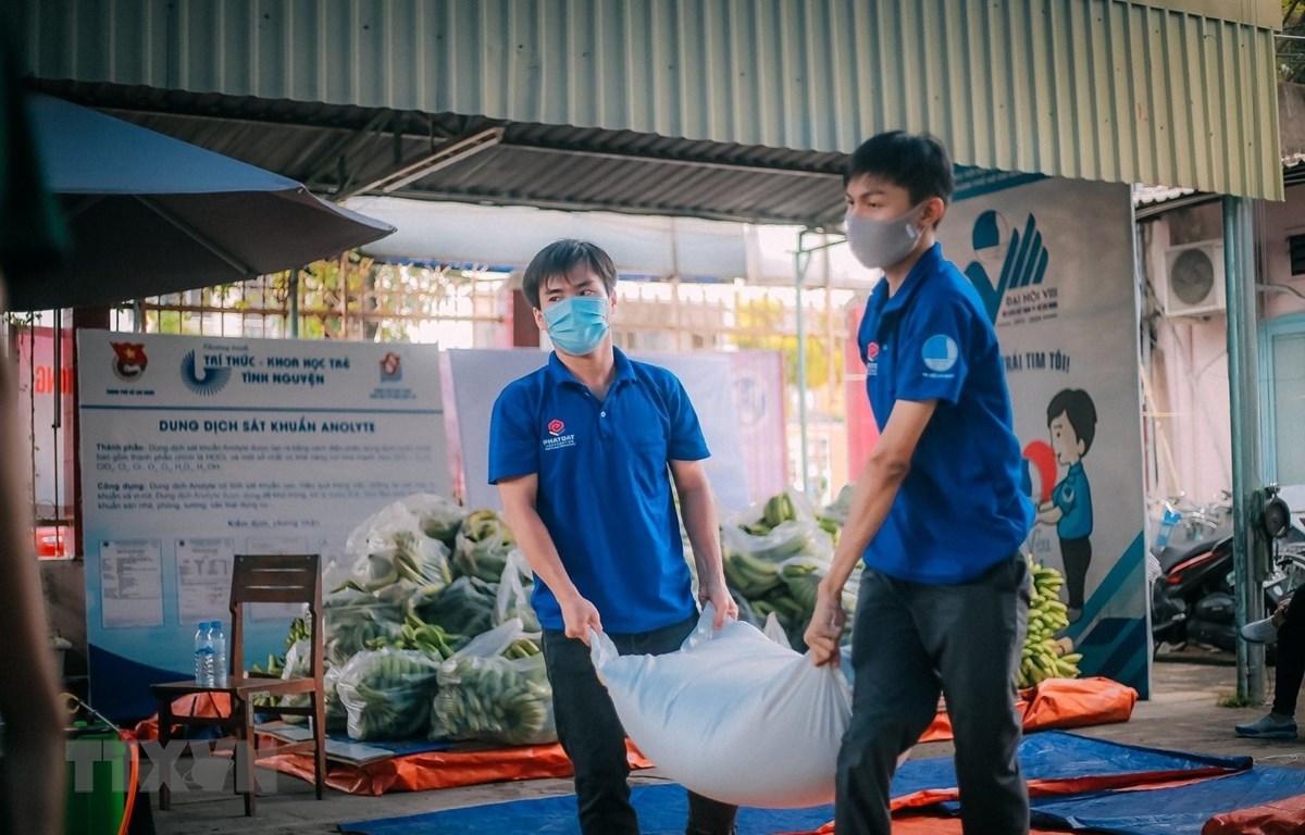 Thanh niên tình nguyện vận chuyển gạo, lương thực cho những hộ dân thuộc khu vực phong tỏa trên địa bàn quận Tân Phú. (Ảnh: Hồng Giang/TTXVN)