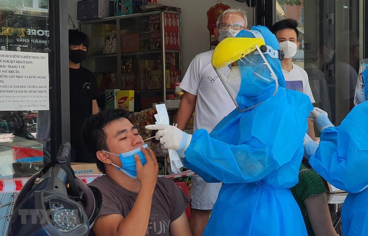Nhân viên y tế lấy mẫu xét nghiệm của người dân quanh khu vực có ca mắc COVID-19 tại đường Lê Duẩn, Đà Nẵng. (Ảnh: Văn Dũng/TTXVN)