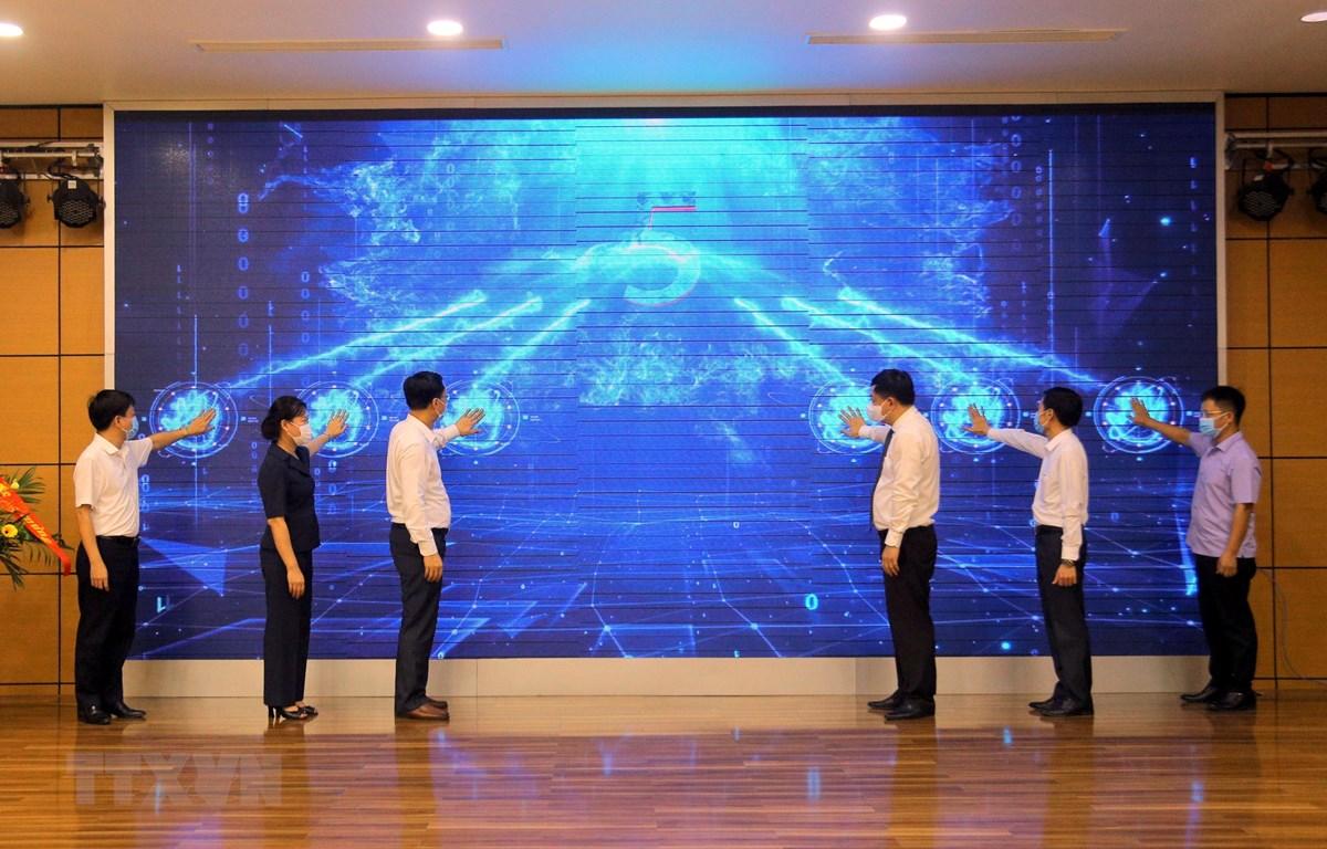 Các đại biểu thực hiện nghi thức khánh thành nâng cấp báo Quảng Ninh điện tử, ứng dụng Quảng Ninh Media trên nền tảng OTT và ra mắt bộ nhận diện thương hiệu Trung tâm với hình ảnh logo QMG. (Ảnh: Đức Hiếu/TXVN)