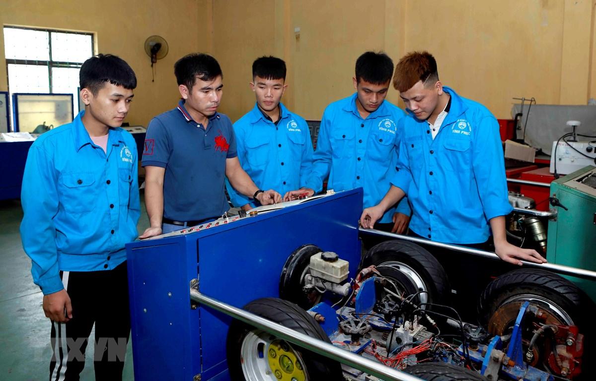 Giáo viên khoa Động lực Trường Cao đẳng nghề Vĩnh Phúc hướng dẫn cho sinh viên cơ chế hoạt động của hệ thống phanh ABS trên ôtô. (Ảnh: Hoàng Hùng/TTXVN)