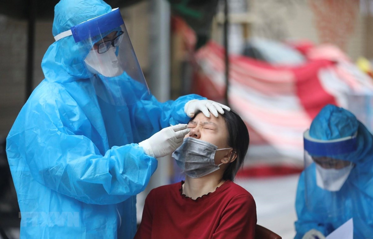 Nhân viên y tế quận Hoàn Kiếm lấy mẫu xét nghiệm COVID-19 cho các trường hợp có nguy cơ cao. (Ảnh: Minh Quyết/TTXVN)
