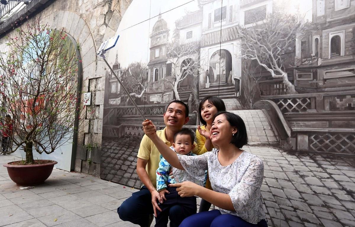 Người dân thủ đô chụp ảnh lưu niệm tại phố Bích họa Phùng Hưng. (Ảnh: Danh Lam/TTXVN)