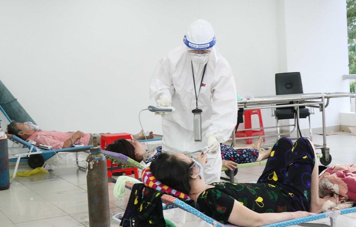 Các bác sỹ thăm khám bệnh nhân nhiễm COVID-19 không triệu chứng có bệnh nền tại Bệnh viện dã chiến thu dung điều trị COVID-19 số 3, thành phố Thủ Đức. (Ảnh: Xuân Khu-TTXVN)