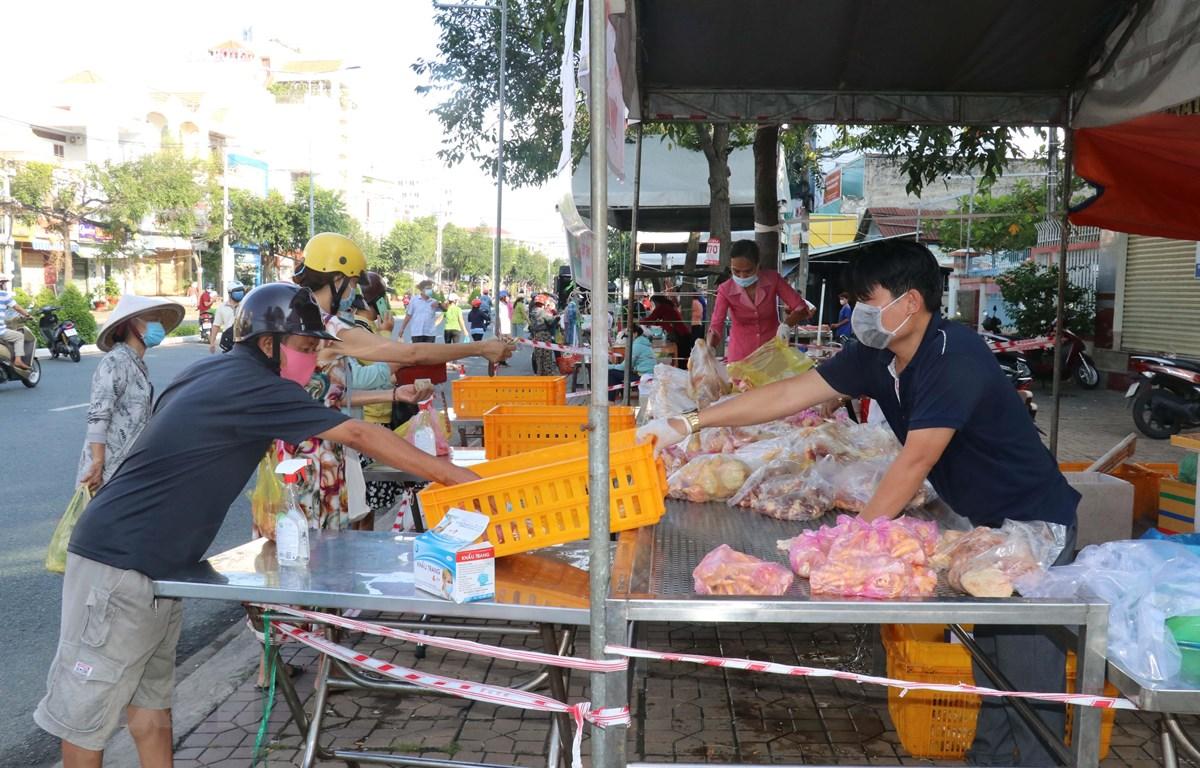Cần Thơ mở thêm nhiều điểm bán thực phẩm ngoài đường phố giúp người dân thuận tiện mua sắm. Người mua và người bán giữ khoảng cách, không tiếp xúc trực tiếp để phòng, chống dịch. (Ảnh: Ngọc Thiện/TTXVN)