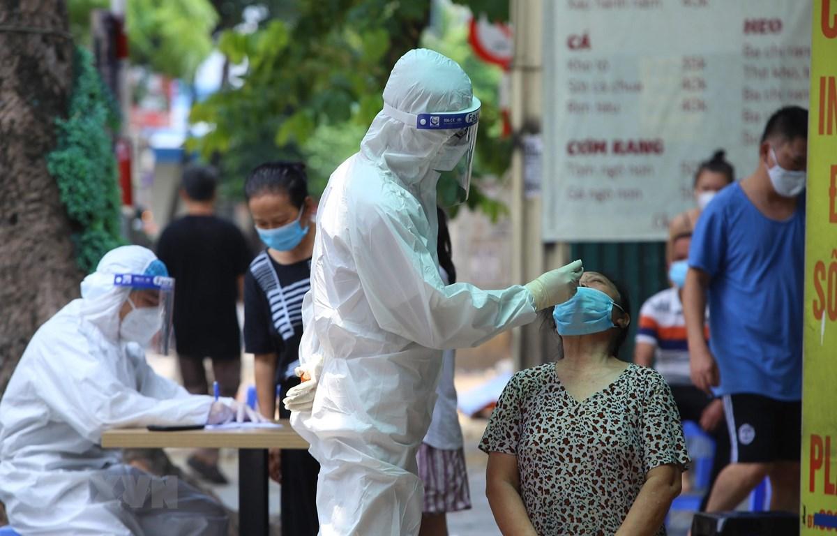 Lực lượng y tế quận Hai Bà Trưng, Hà Nội lấy mẫu xét nghiệm cho người dân phố Tô Hiến Thành. (Ảnh: Hoàng Hiếu/TTXVN)