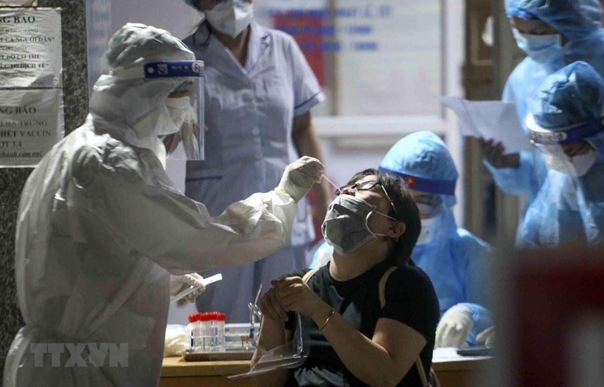 Nhân viên y tế lấy mẫu xét nghiệm COVID-19 cho những người có nguy cơ mắc COVID-19 tại Bệnh viện Phổi Hà Nội. (Ảnh: Tuấn Đức/TTXVN)