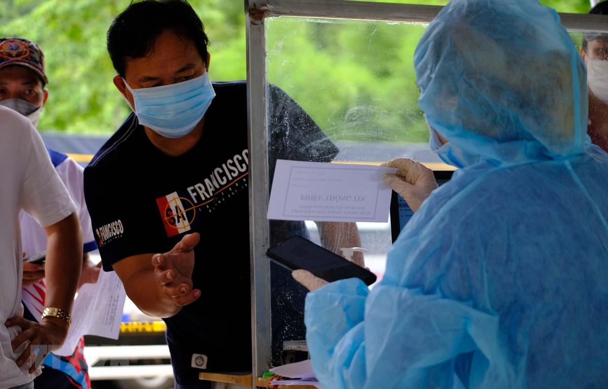 Lực lượng y tế kiểm tra lại thông tin của một tài xế tại khu vực khai báo y tế, xuất trình các giấy tờ liên qua khi đi qua trạm kiểm soát COVID-19 trên quốc lộ 20, tỉnh Lâm Đồng. (Ảnh: Nguyễn Dũng - TTXVN)