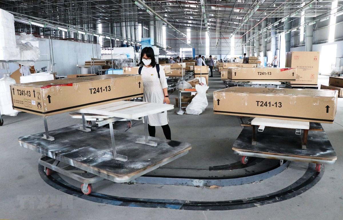Đóng gói và kiểm tra lô hàng đồ gỗ xuất khẩu sang thị trường Mỹ tại Công ty Triệu Phú Lộc (Bình Dương). (Ảnh: TTXVN)