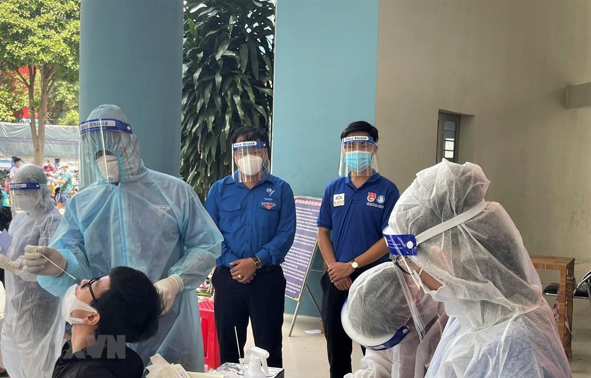 """Nhân viên y tế lấy mẫu test nhanh """"quét"""" F0 trên địa bàn thành phố Dĩ An (Bình Dương). (Ảnh: TTXVN phát)"""