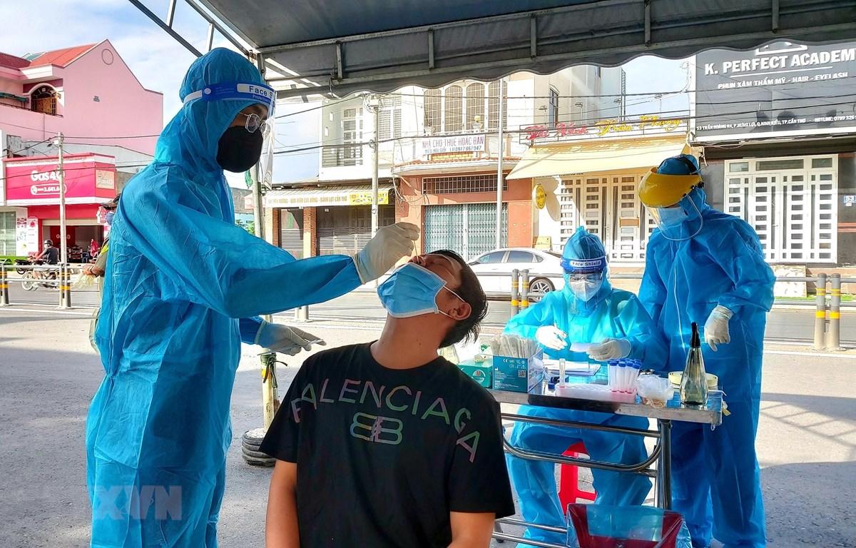 Nhân viên y tế lấy mẫu xét nghiệm cộng đồng cho người dân ở Khu vực 2, phường Hưng Lợi, quận Ninh Kiều. (Ảnh: Thu Hiền/TTXVN)