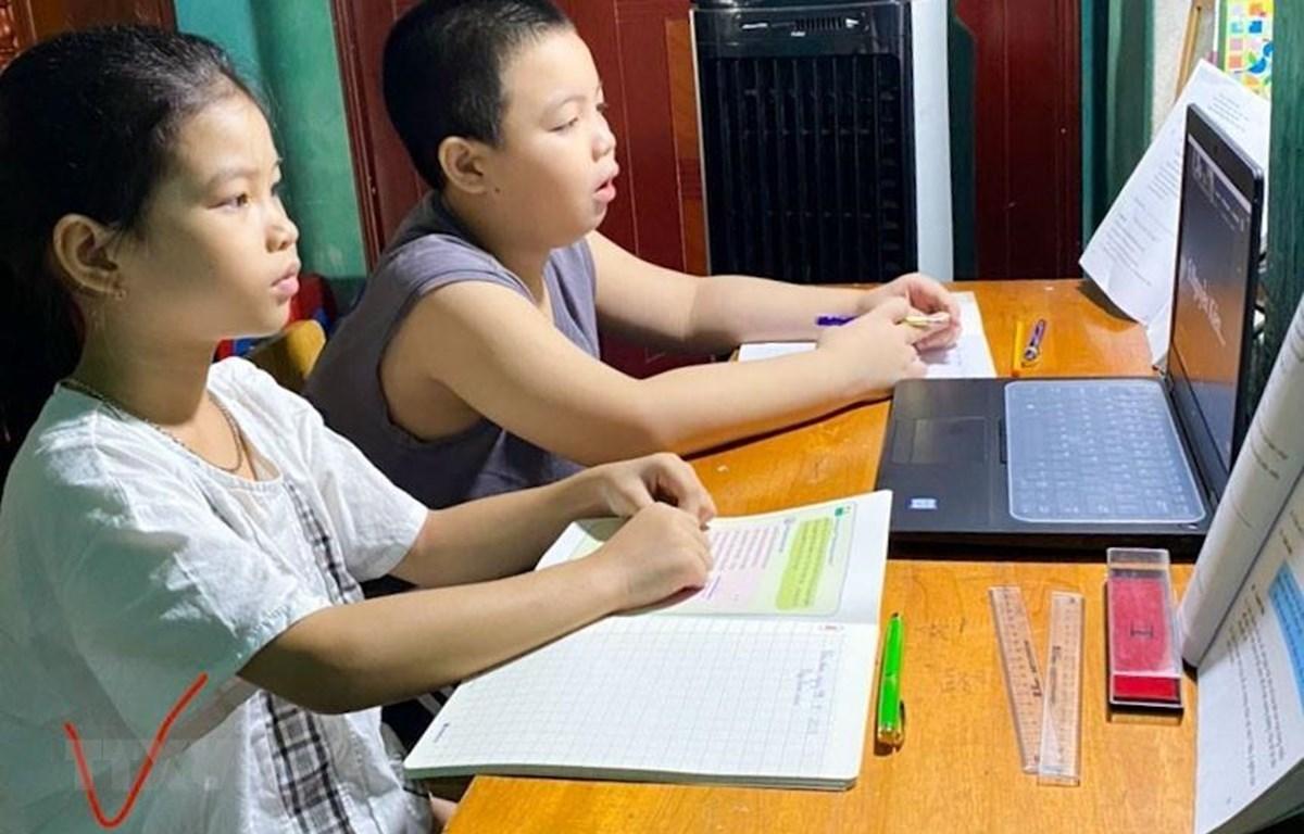 Nhiều trường hợp 2 học sinh phải học chung trên một thiết bị. (Ảnh: TTXVN phát)