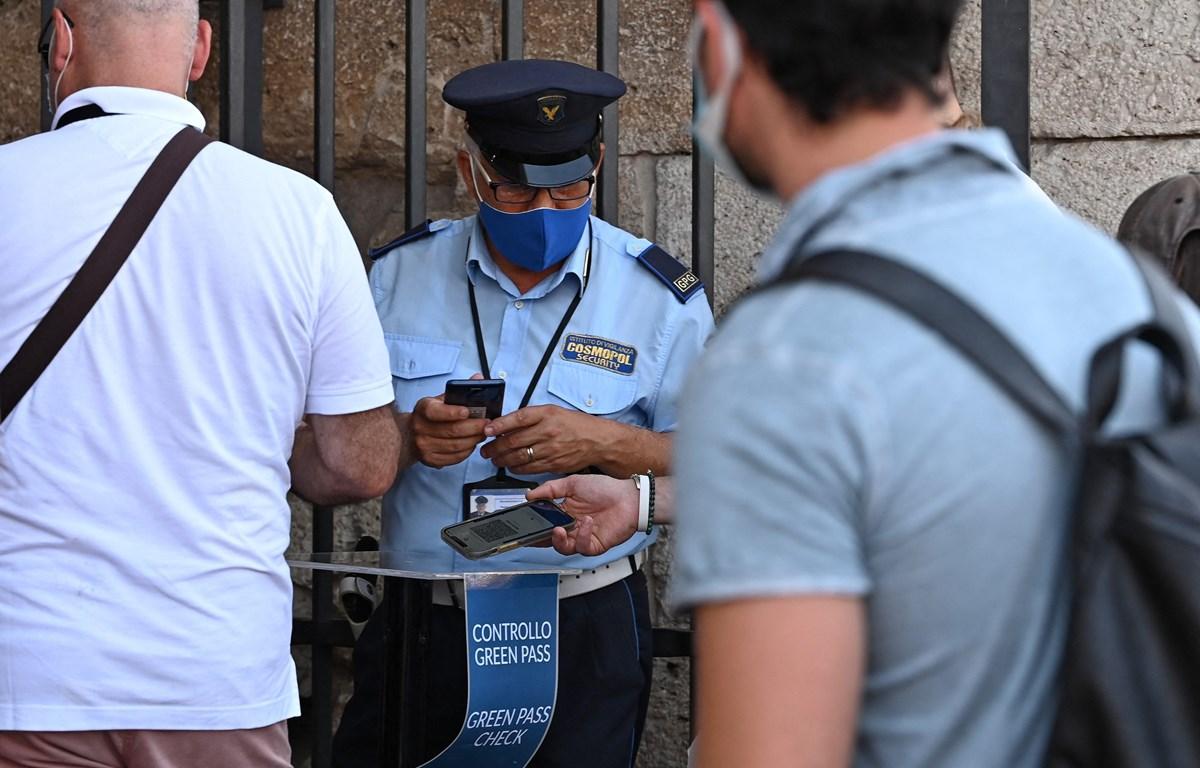 Nhân viên an ninh kiểm tra chứng nhận COVID-19 của khách tham quan tại Rome, Italy, ngày 6/8/2021. (Ảnh: AFP/TTXVN)
