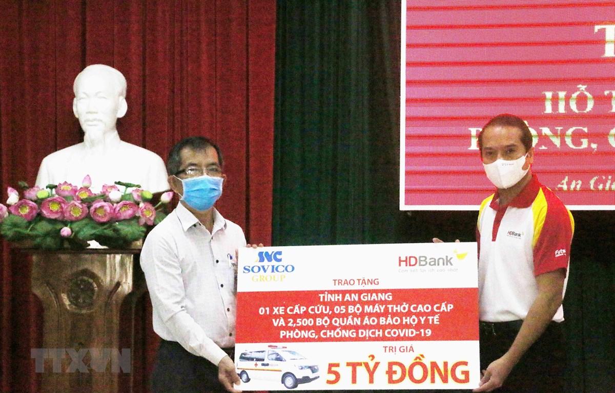 Đại diện Tập đoàn Sovico và Ngân hàng Thương mại Cổ phần Phát triển Thành phố Hồ Chí Minh HDBank (phải) trao bảng tượng trưng tăng tỉnh An Giang 1 xe cấp cứu, 5 máy thở cao cấp, 2.500 bộ quần áo bảo hộ y tế. (Ảnh: Công Mạo/TTXVN)