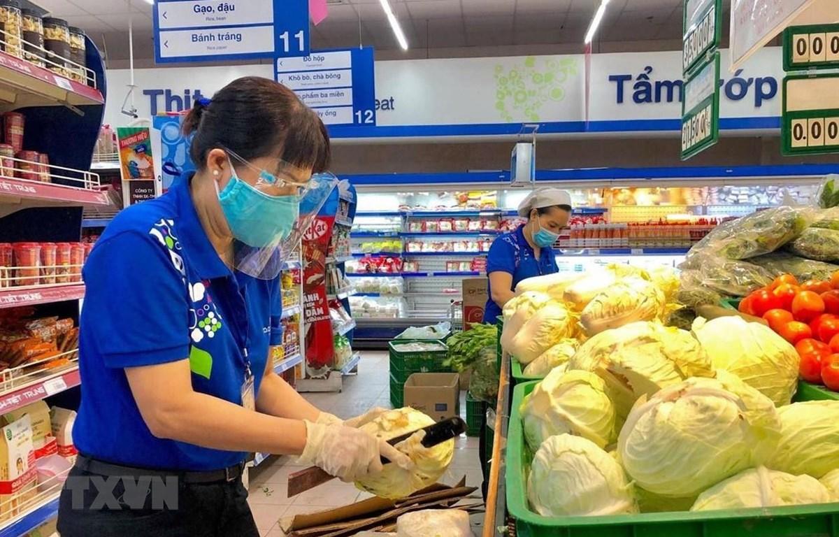 Nhân viên siêu thị Thành phố Hồ Chí Minh bổ sung hàng hóa lên kệ phục vụ khách hàng mua sắm trực tiếp. (Ảnh: TTXVN phát)