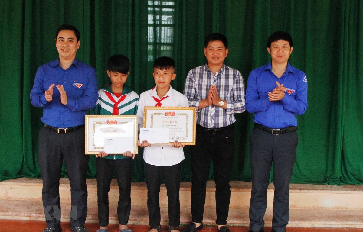 Trao bằng khen của Tỉnh đoàn và tiền thưởng cho hai em học học sinh Nguyễn Văn Chương và học sinh Nguyễn Phi Anh. (Ảnh: Phan Quân/TTXVN)