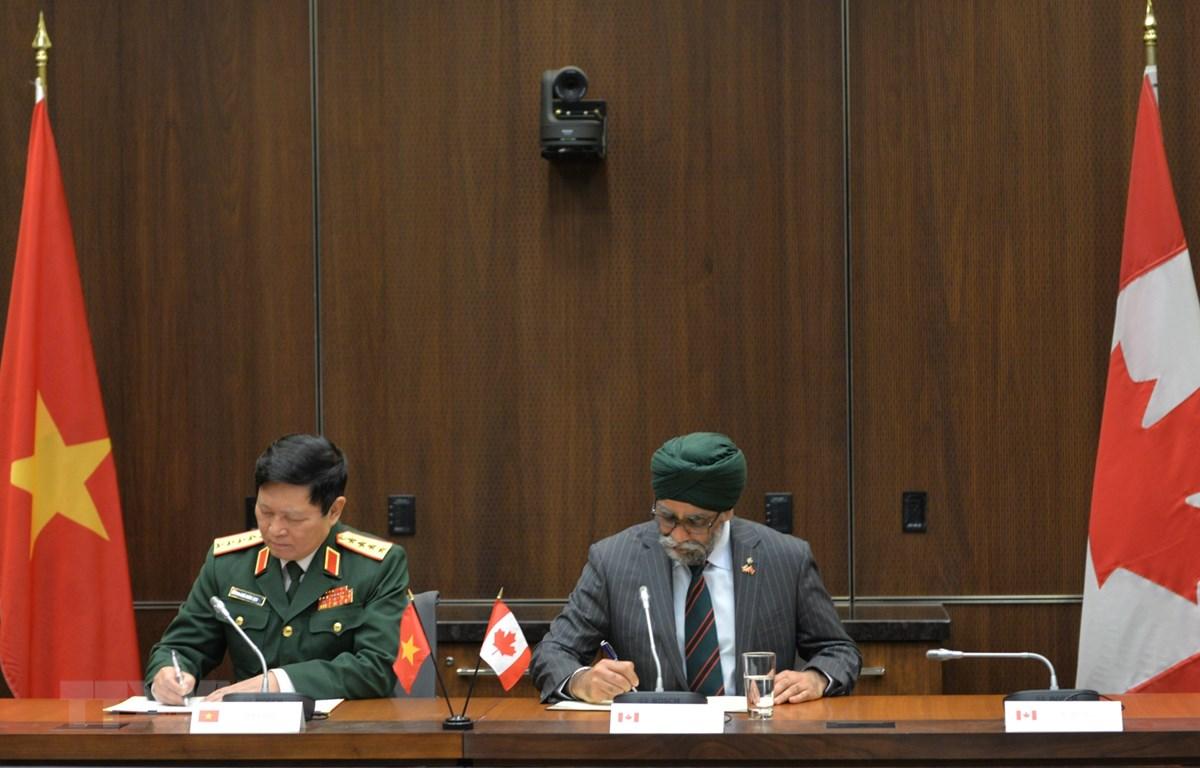 Bộ trưởng Quốc phòng hai nước ký Bản ghi nhớ giữa Bộ Quốc phòng Việt Nam và Bộ Quốc phòng, Lực lượng vũ trang Canada. (Ảnh: Vũ Quang Thinh/TTXVN)