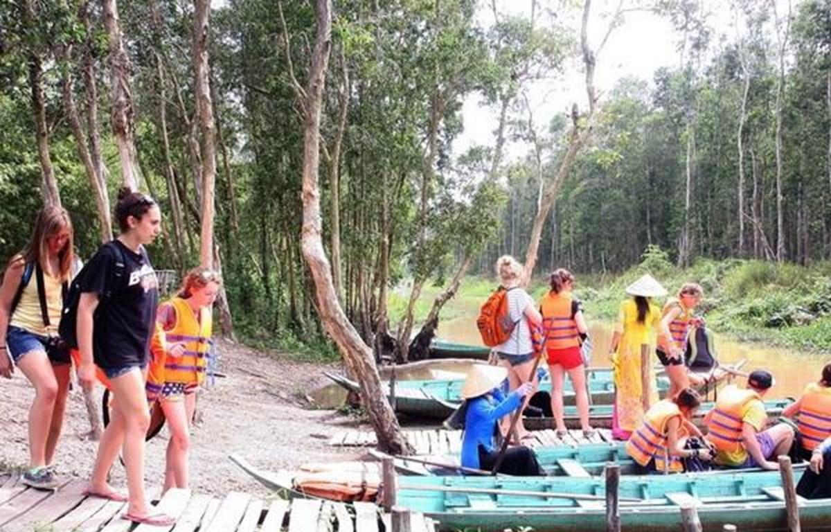 Du khách quốc tế tham quan khu du lịch Gáo Giồng, huyện Cao Lãnh vào mùa nước nổi. (Ảnh: Đình Huệ/TTXVN)