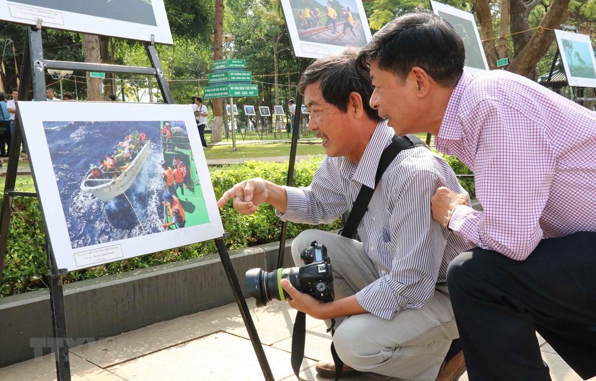 Các đại biểu và người dân thưởng lãm các tác phẩm ảnh nghệ thuật. (Ảnh: Hoài Nam/TTXVN)