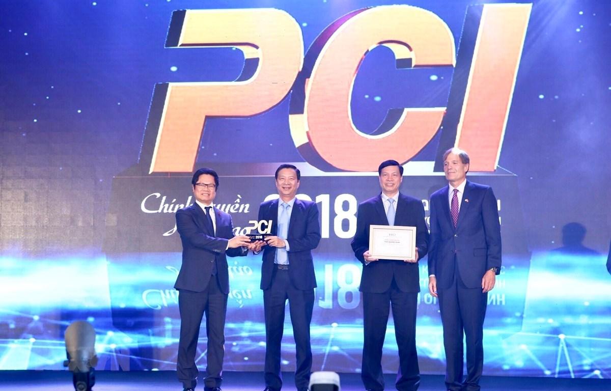 Ban tổ chức trao kỷ niệm chương cho tỉnh Quảng Ninh quán quân PCI năm 2018. (Ảnh: Minh Quyết /TTXVN)