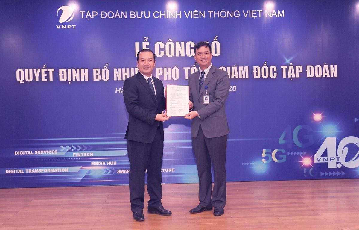 Ông Phạm Đức Long trao quyết định Phó Tổng Giám đốc cho ông Nguyễn Nam Long (phải). (Ảnh: CTV/Vietnam+)