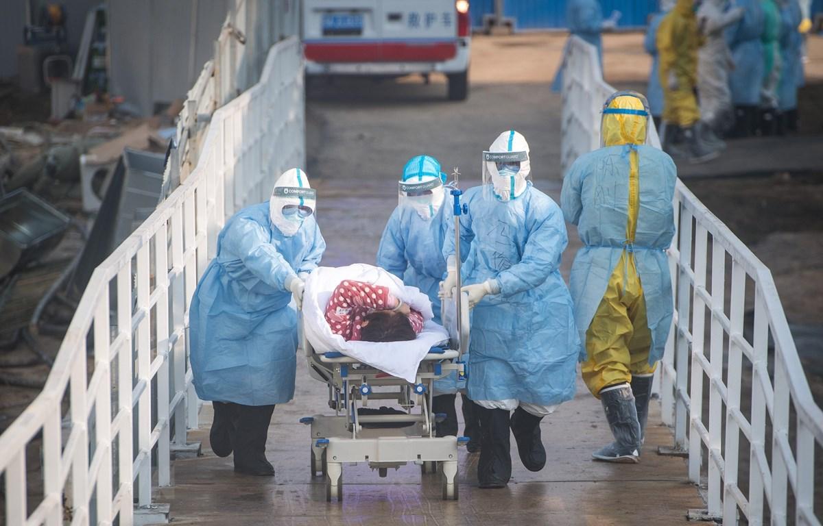 Nhân viên y tế vận chuyển người mắc bệnh COVID-19 tới bệnh viện dã chiến tại Vũ Hán. (Ảnh: THX/TTXVN)