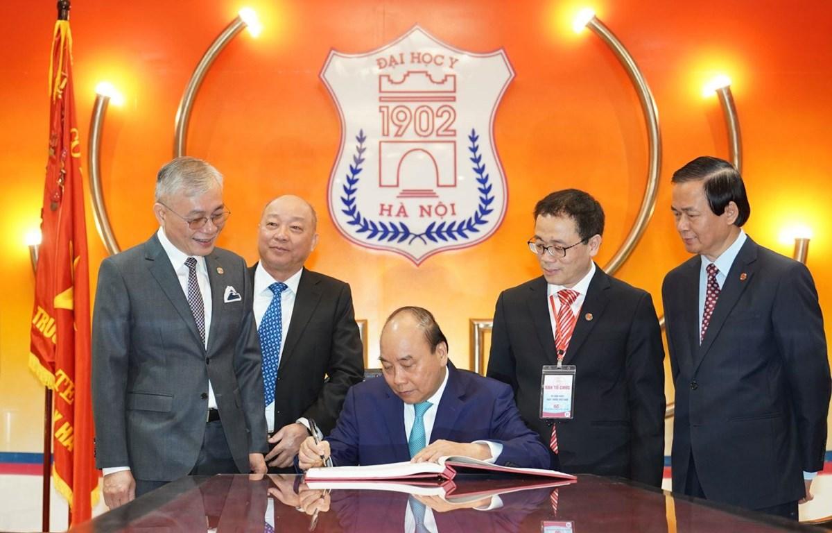 Thủ tướng Nguyễn Xuân Phúc đến dự Lễ kỷ niệm 65 năm Ngày Thầy thuốc Việt Nam tại Trường Đại học Y Hà Nội và viết vào sổ lưu niệm. (Ảnh: PV/Vietnam+)