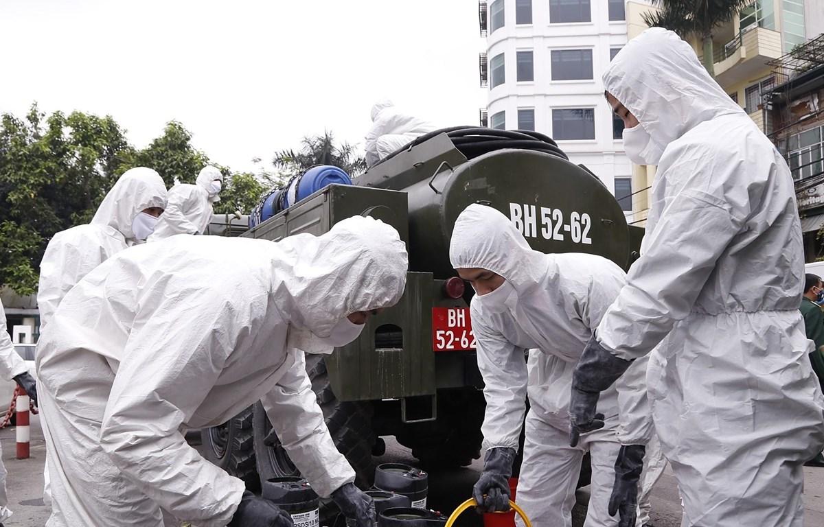 Lực lượng hóa học pha hóa chất để tiến hành phun tiêu tẩy khu vực phố Trúc Bạch, quận Ba Đình. (Ảnh: Dương Giang/TTXVN)