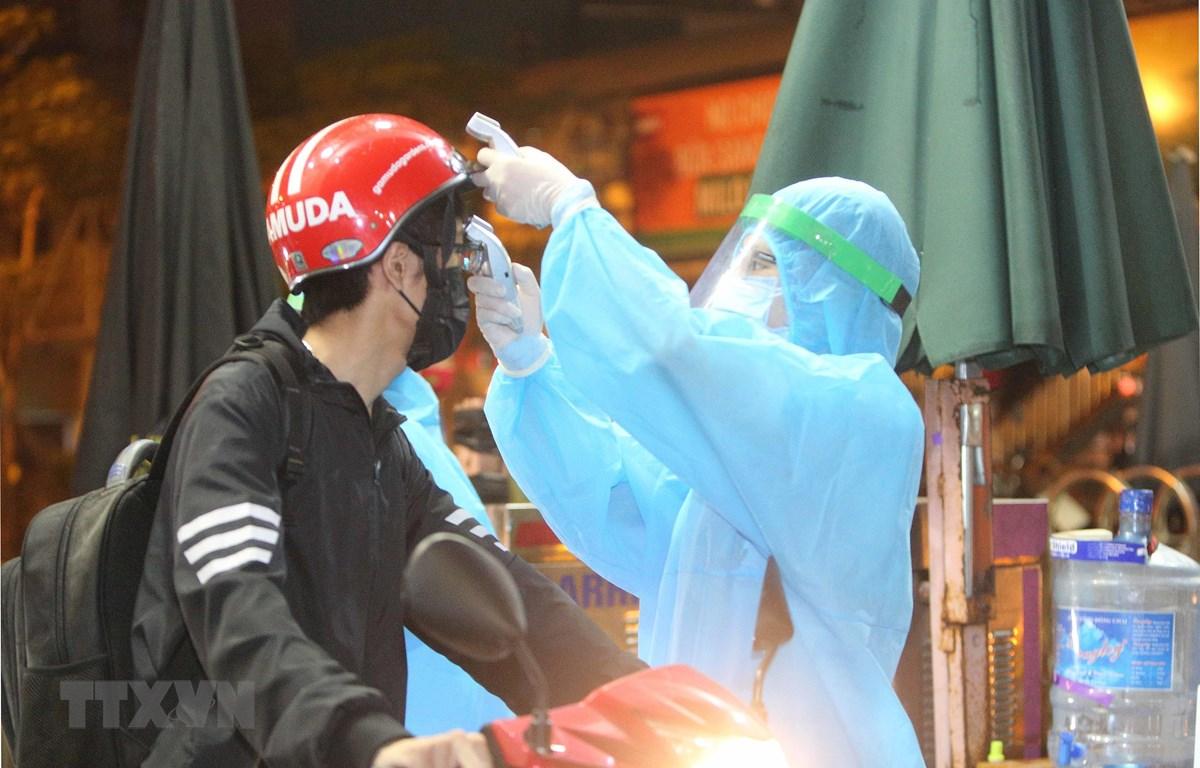 Nhân viên y tế kiểm tra và sát khuẩn cho những người vào bênh viện. (Ảnh: Dương Giang/TTXVN)